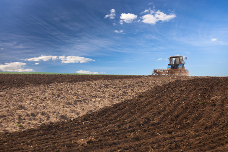 plough machine: Agricultural Lanscape - Tractor working on the field - spring sunny day Stock Photo