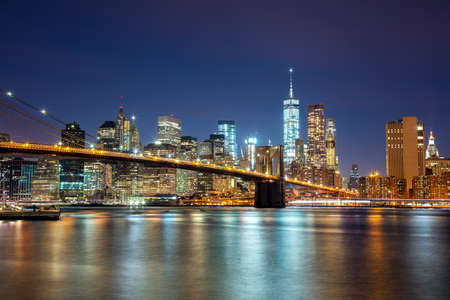 nacht: New York - Ansicht von Manhattan Skyline mit Wolkenkratzern und berühmten Brooklyn Bridge bei Nacht und Stadt Beleuchtung, USA