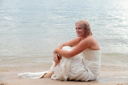 Bride sitting in thoughtful pose on the beach. photo