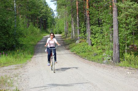 Woman cycling in rural Finland photo