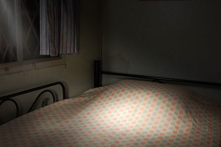 bedspread: A made bed lit from outside at night Stock Photo