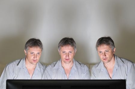 clones: Three identical clones or triplets watching television or a computer screen together