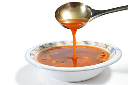 broth: Pouring minestrone soup into a bowl with a ladle isolated on white