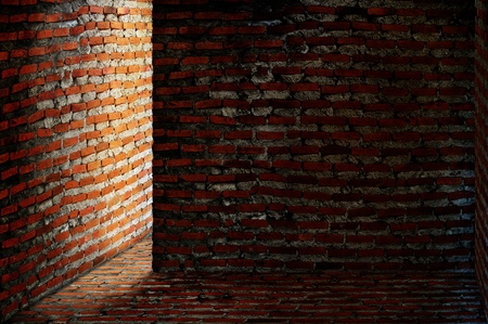 Dark brick room with light shining around a corner photo