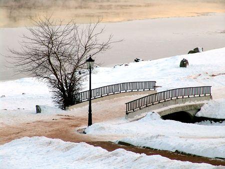 A bridge in a winter park with a lantern photo