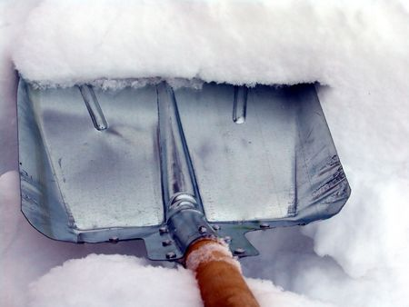 Cleaning snow with a metallic shovel photo