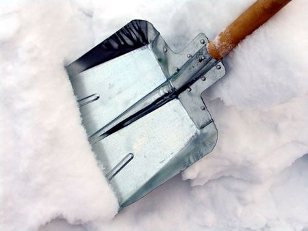 clearing the path: Cleaning snow with a shovel Stock Photo