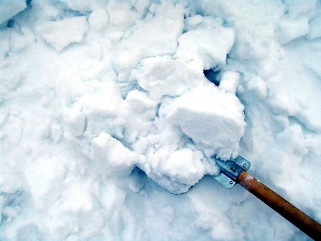 clearing the path: Cleaning snow with a metallic shovel Stock Photo
