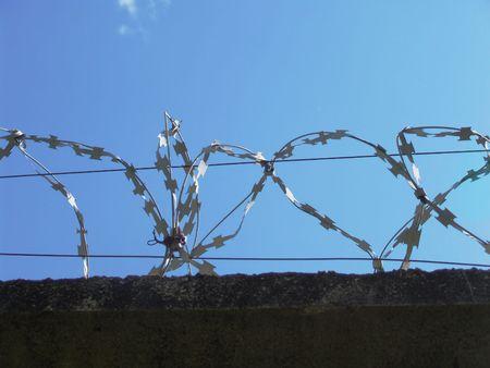 delimit: Razor wire above a wall