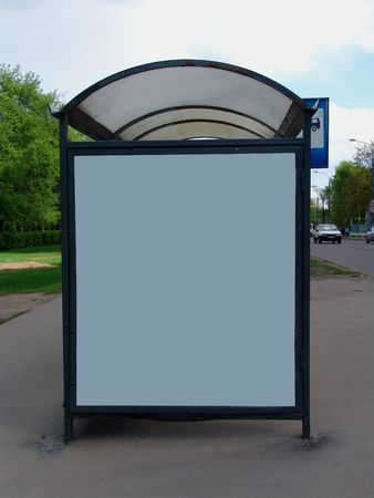 bus station: A bus station with a park behind and an empty ad panel