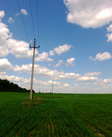 telephone poles: Telephone poles on a green field with a blue sky with clouds Stock Photo