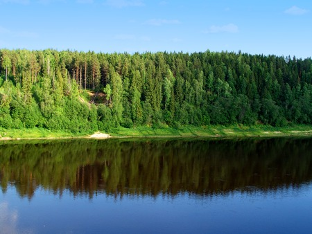 A river, a forest on a hill reflecting in water and a blue sky photo