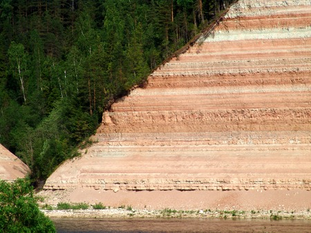 A cliff with a forest and visible ground layers photo