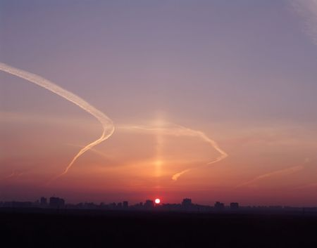 sihlouette: A sunrise with a megapolis background view and a clear sky with planes trailers