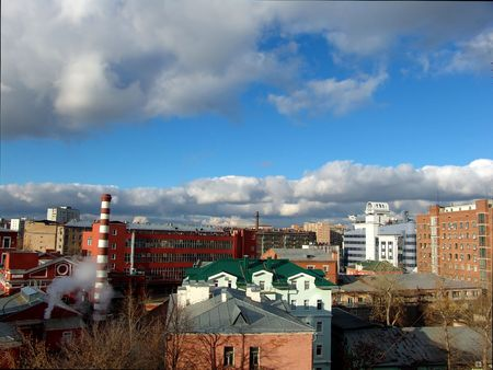 A view over city roofs with industrial and office buildings and a nice cloudy sky photo