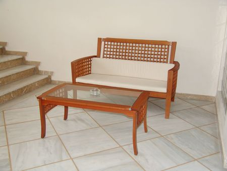 A wooden and glass table and chair in a hotel hall photo