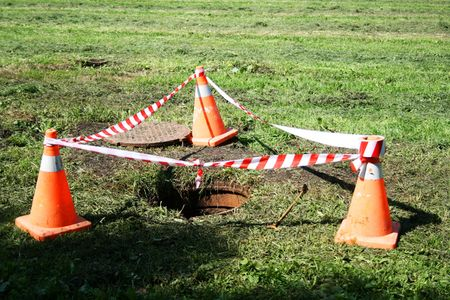 roadworks: A sewage entrance surrounded with roadworks cones