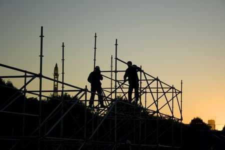 Silhouettes of two builders constructing something in the evening Stock Photo - 2370486