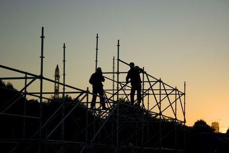 the yards: Siluetas de dos constructores de la construcci�n de algo en la noche Foto de archivo