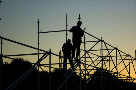 Silhouettes of two builders constructing something in the evening photo