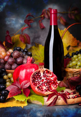 Beautiful still life with wine glasses, grapes, pomegranate on the table photo