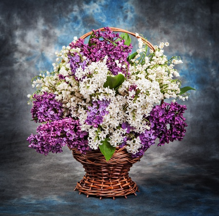 Still life, a beautiful lilac and lily of the valley in the basket photo