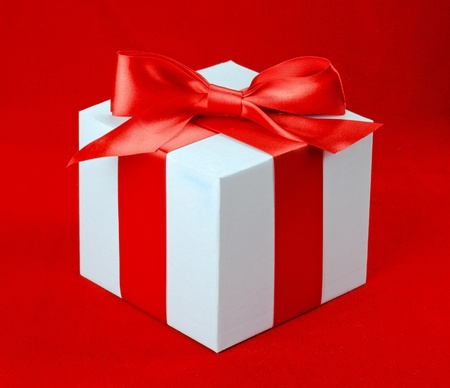 White box, bow and ribbon on red background  photo