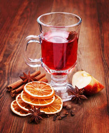 Glass of mulled wine on the table in dark wood. The dried oranges, anise and cinnamon photo
