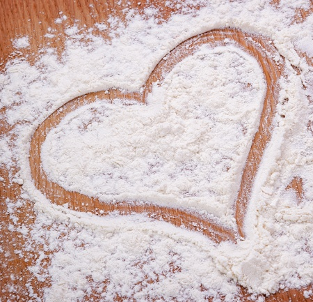 cookie cutter: Heart drawn with flour on the kitchen table. Food ingredient