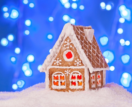 Gingerbread house in the snow with a beautiful New Year's background Stock Photo - 21535442