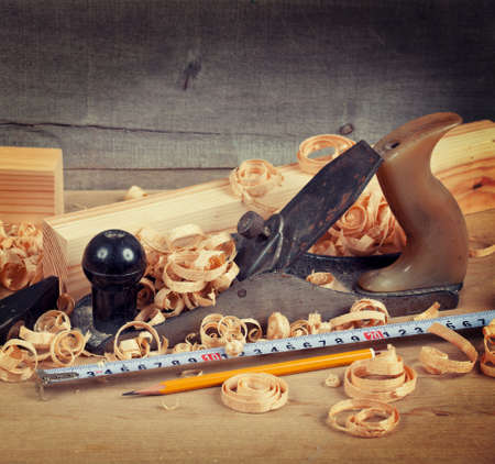 Wood planer, shavings and hand tools on board Stock Photo