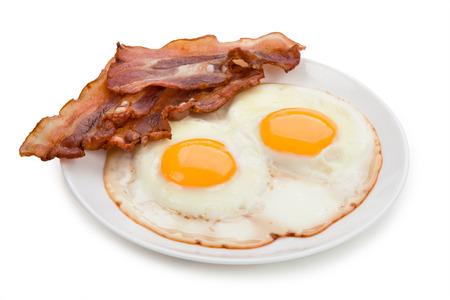 huevos fritos: Placa con huevos fritos, tocino aislado en fondo blanco