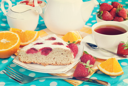 Cake with strawberries and breakfast on the table. Vintage retro hipster style version photo