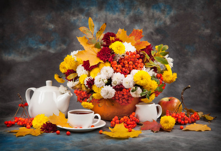 colorful still life: Autumn still life. Tea, flower and yellow leaves