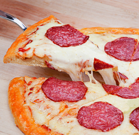 flavorful: Sliced fresh flavorful pepperoni pizza on wood Stock Photo