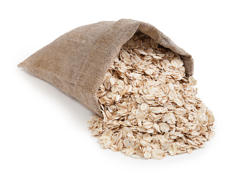 burlap sack: Rolled oats in a bag isolated on white background Stock Photo
