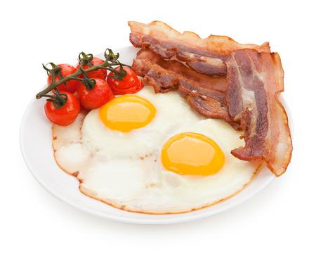 huevos fritos: Placa con huevos fritos, tocino aislado.