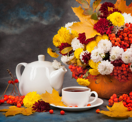 colorful still life: Autumn still life with Tea, flowers and yellow leaves.