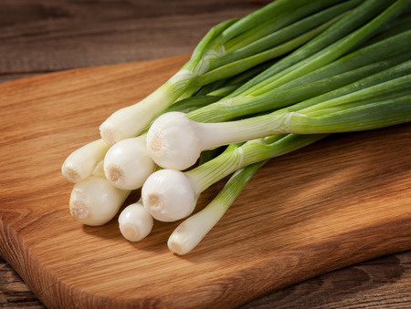 spring onions: Fresh Onions laying on a board. Stock Photo