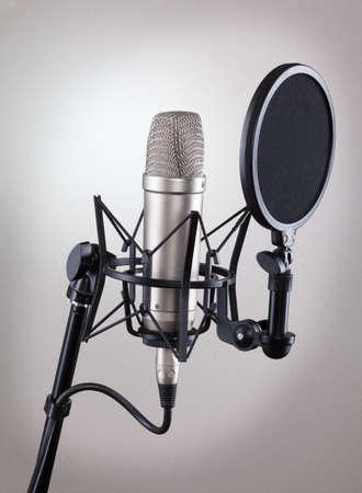 microfono de radio: Micrófono del estudio en un fondo gris.