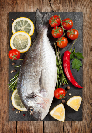 gilt head: Fresh fish, lemon, spices and cherry tomatoes on a stone board Stock Photo