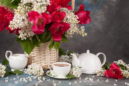 mazzo di fiori: Bouquet di rose con lilla e tazze da tè per tè sul tavolo
