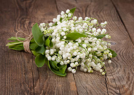 brown white: lilies of the valley on the old boards Stock Photo