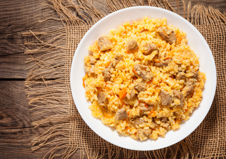 A delicious pilaf in a dish on the old board Stock Photo