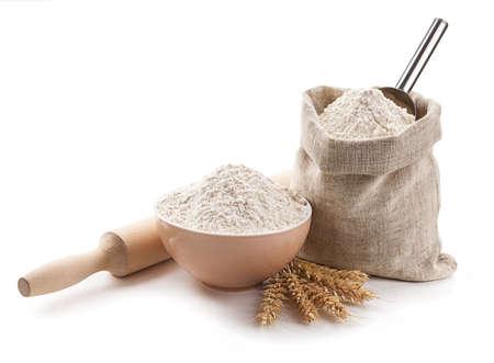 flour: utensilios de cocina, las orejas, la harina en un bol y la bolsa aislados. Foto de archivo