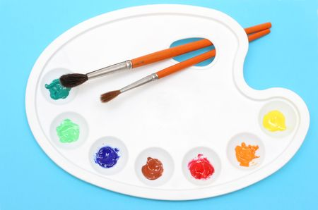 Painters pallete with paintbrushes on blue background photo