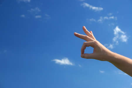 akkoord: OK hand tekenen tegen de blauwe hemel