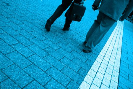 saturated: Blue toned photo of two business men walking, highly saturated