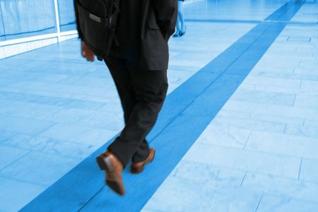 blue toned: Blue toned motion photo of businessman walking, focus on his right arm