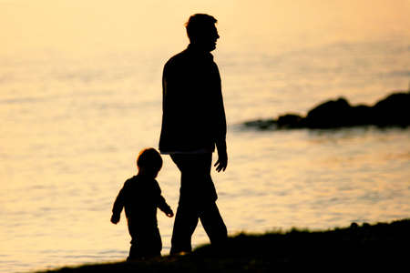 follow: Father and Son walking by the sea Stock Photo
